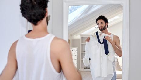 Mann steht vorm Spiegel und probiert Outfit an.
