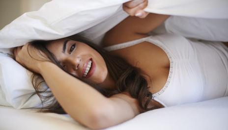 Junge, lächelnde Frau liegt im Bett.
