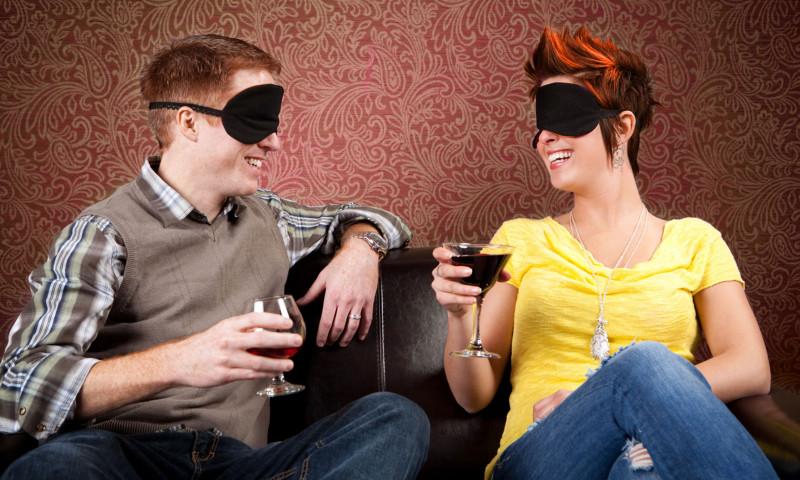 Junges Paar sitzt sich mit verbundenen Augen gegenüber und trinkt Wein.