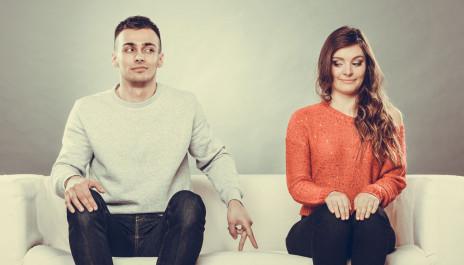 Schüchterne Paar sitzt nebeneinander auf einer Couch.