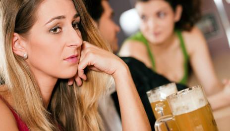 Verzweifelte Frau sitzt an der Bar.