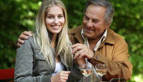 Junge Frau und älterer Mann trinken Wein.