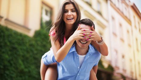 Junge Frau sitzt Huckepack auf einem jungen Mann.