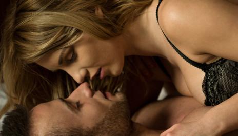 Junges Paar liegt im Bett und küsst sich.