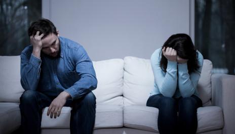 Weinende Frau sitzt neben verzweifeltem Mann auf der Couch.