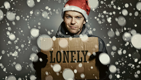 """Mann steht im Schnee und hält Pappschild mit der Aufschrift """"Lonely"""" hoch"""