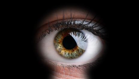 Das Auge einer Frau durch ein Schlüsselloch betrachtet.