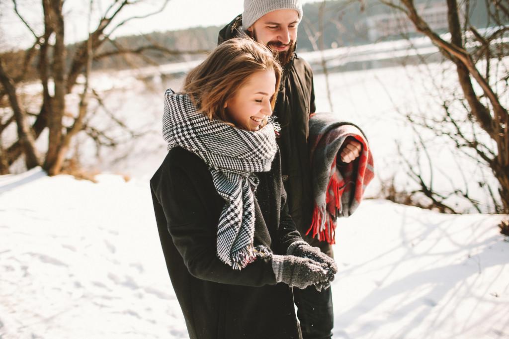 Date-Idee im Winter: Junges Paar spaziert im Schnee an einem gefrorenen See entlang