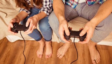 Junges Paar sitzt auf dem Sofa und hält Gamepads in der Hand