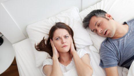 Frau hält sich wütend die Ohren zu, während der Mann schnarcht
