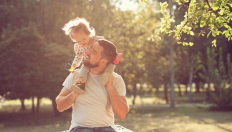 Vater werden lohnt sich. Ein Vater trägt kleine Tochter Huckepack