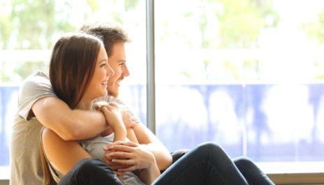 Glückliches Paar sitzt Arm in Arm vor dem Fenster