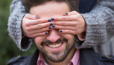 Frau hält Mann bei einem Blind Date die Augen zu