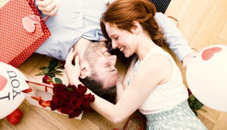 Mann und Frau liegen auf dem Boden zwischen Valentinstagsgeschenken, Blumen und Ballons.