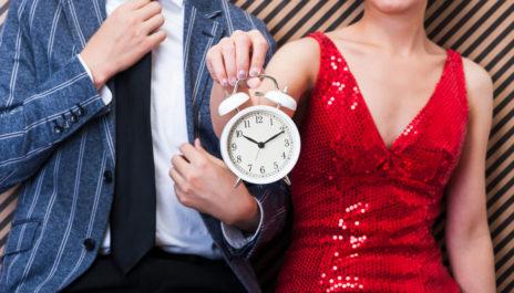 Frau steht bei einem Speed-Dating neben einem Mann und hält einen Wecker in der Hand.