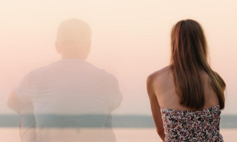 Frau sitzt neben Mann, der langsam unsichtbar wird.