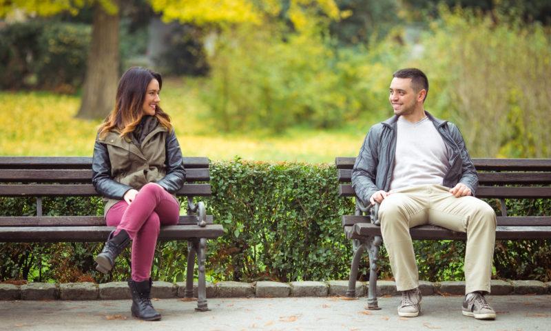 Mann und Frau sitzen auf Parkbank nebeneinander und flirten